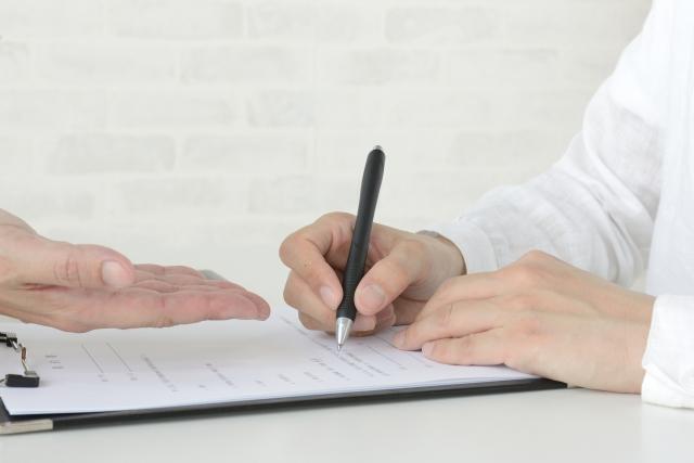 契約書にサインしている