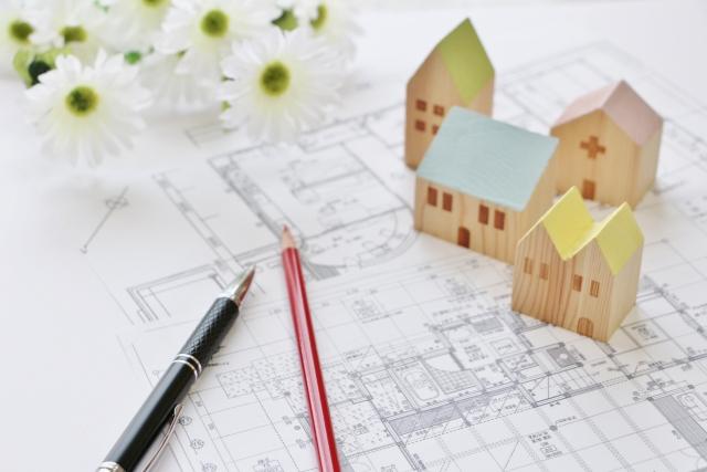 建築図面の上に家の模型とペンが乗っている