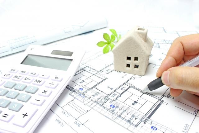 建築図面の上に家の模型と電卓が乗っている