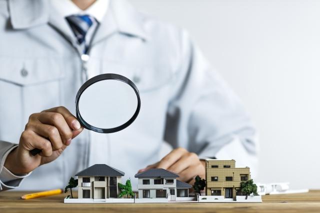 建築業者がルーペで家の模型をみている