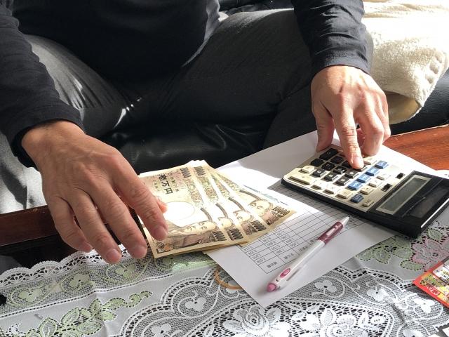 電卓でお金の計算をしている