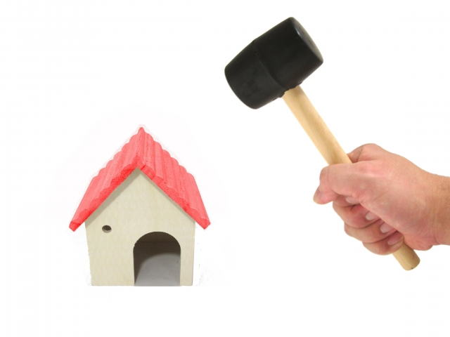 ハンマーで模型の家を叩こうとしている