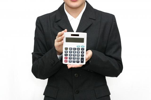 スーツ着た人が電卓を持っている