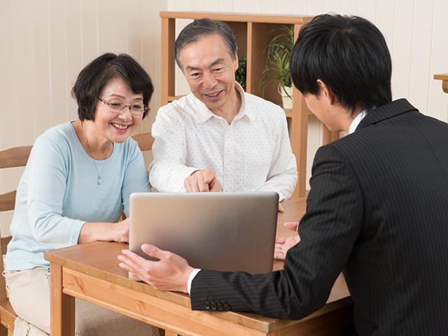 老夫婦とスーツ着た営業男性とパソコンを見て打ち合わせしている