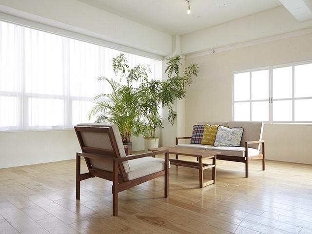 リビング真ん中に木製のソファーとテーブルが置いてある