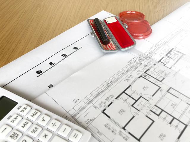 建築図面の上に印鑑と電卓が乗っている