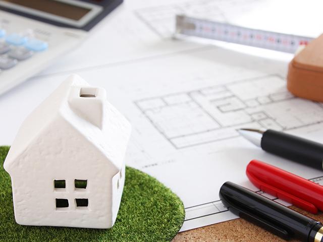 家の模型と建築図面とペンとメジャー