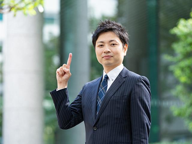 スーツを着た男性が人差し指を立てている