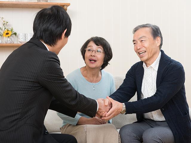 営業男と老夫婦が握手している