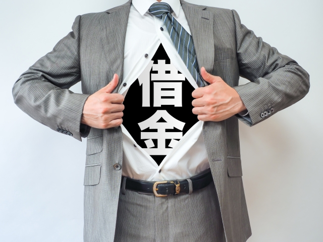 スーツを着た男性のTシャツに借金の文字